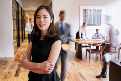 woman with arms crossed in front of busy office