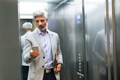 old man in elevator holding phone