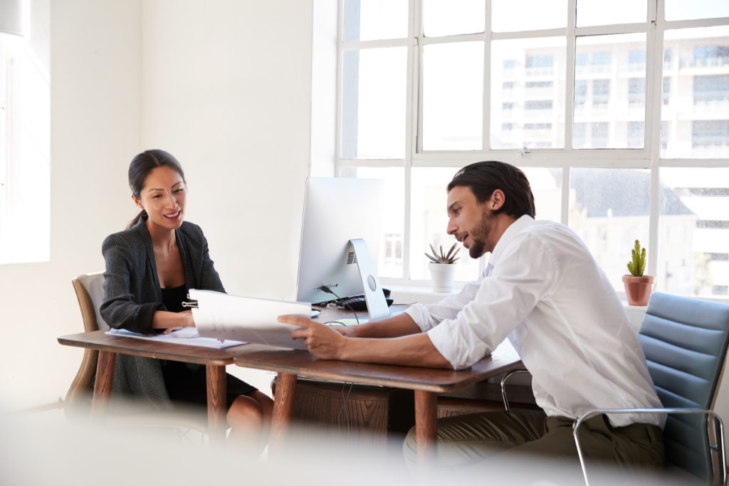 two people working together at desk